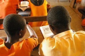 Imagen niños africanos leyendo libro electrónico